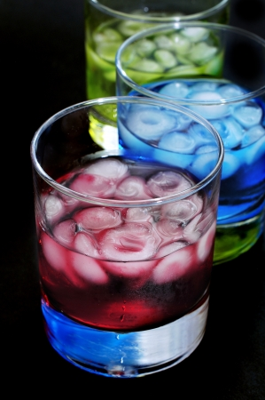 thirstiness: closeup of some glasses with mixed drinks of different colors in a club