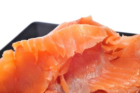 closeup of a black plate with some slices of smoked salmon on a white background photo