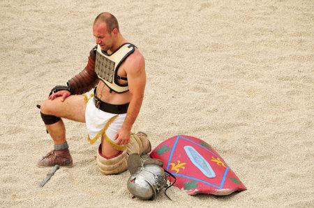 fight arena: Tarragona, Spain - May 26, 2012: Gladiator on the arena of Roman Amphitheater in Tarragona, Spain. Every year, the historic recreation program TarracoViva recreates a gladiators fight
