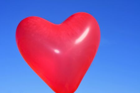 a red heart-shaped balloon over the blue sky Stock Photo - 14476263
