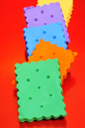 closeup of some fake plasticine cookies of many colors on a red background photo