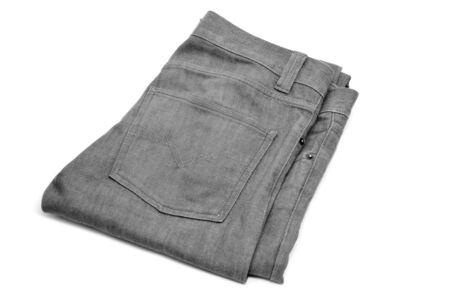 folded gray denim trousers on a white background photo