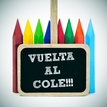 secondary education: sentence back to school written in spanish, vuelta al cole, in a blackboard label and some crayons of different colors in the background