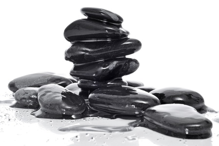a pile of balanced zen stones covered with water on a white background photo