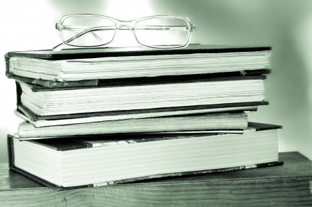 cramming: a pile of books and a pair of glasses symbolizing the concept of reading habit or studying Stock Photo