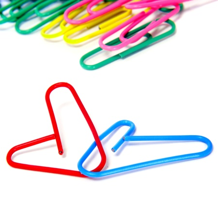 closeup of some paperclips, two of them in the shape of a heart, on a white background photo