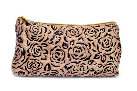 a beige case or toilet bag patterned with black flowers on a white background photo