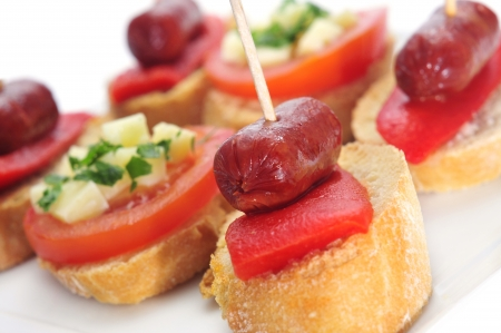 chorizos: closeup of a plate with different spanish pinchos, like those made with chorizos an red pepper, or tomato and cheese