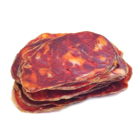 some slices of red spanish chorizo, a spicy smoked sausage, on a white background photo