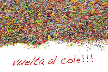 vuelta al cole, back to school written in spanish, on a white background and a pile of crayon shavings of different colors photo