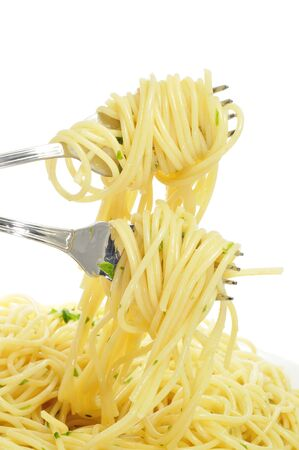 closeup of a plate with spaghetti and two forks with spaghetti rolled on them photo