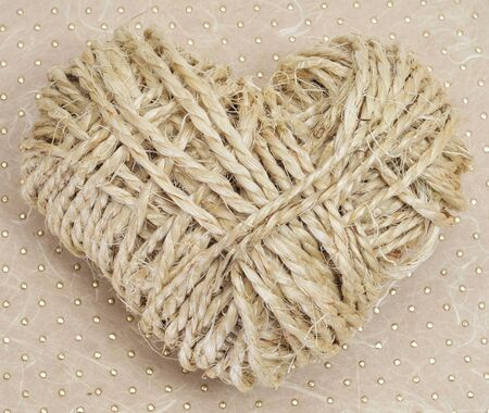heart-shaped coil of rope on a textured background photo