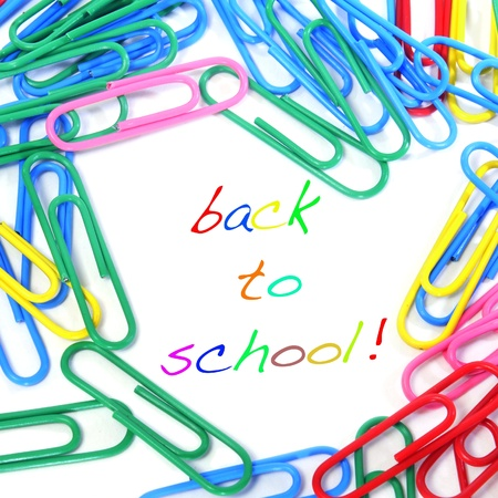 sentence back to school written in different colors and a pile of colorful paper clips photo