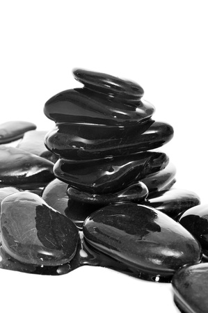 chill out: a pile of balanced zen stones covered with water on a white background