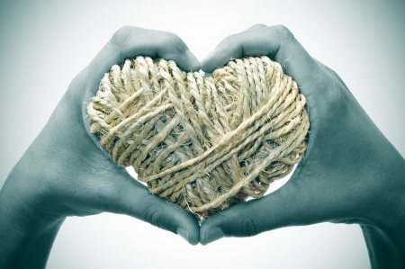 man hands forming a heart showing a heart-shaped coil of rope Stock Photo