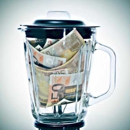 licuadora: una pila de billetes de 50 euros en una licuadora que simboliza la devaluación del euro Foto de archivo