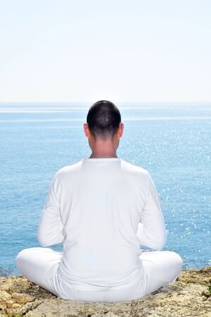 someone dressed in white meditating on the beach Stock Photo - 14961771