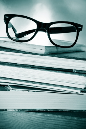 a pile of books and glasses on a desk symbolizing the concept of reading habit or studying photo