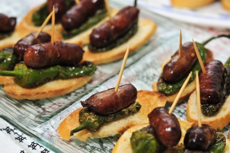 closeup of a plate with spanish pinchos made with chorizos an Padron peppers Stock Photo - 15031499