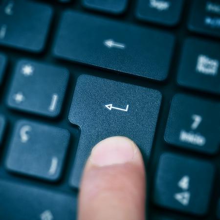 tecla enter: alguien presionando enter en el teclado del ordenador Foto de archivo