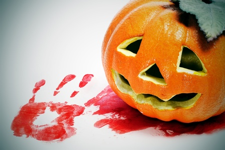 a jack-o-lantern on a blood pool and a bloody handprint Stock Photo - 15117612