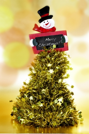 tinsel christmas tree and a blackboard with the sentence merry christmas written on it photo