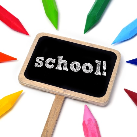 word school written on a blackboard and some crayons of different colors on a white background Stock Photo - 15499116