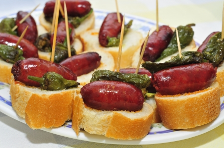 closeup of a plate with spanish pinchos made with chorizos an Padron peppers Stock Photo - 15222538
