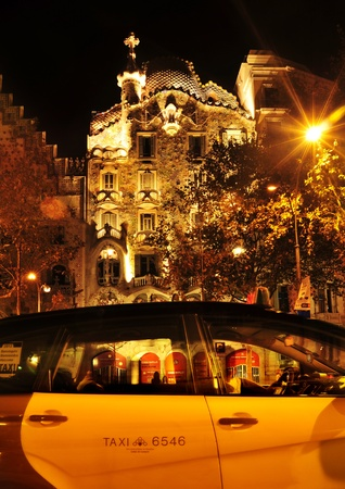 Barcelona, Spain - September 10, 2012: Casa Batllo at night and a typical yellow and black taxicab in Barcelona, Spain. The famous building was designed by Antoni Gaudi