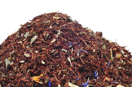 herbolaria: un montón de té rooibos mezclado con frutas secas y hierbas sobre un fondo blanco Foto de archivo
