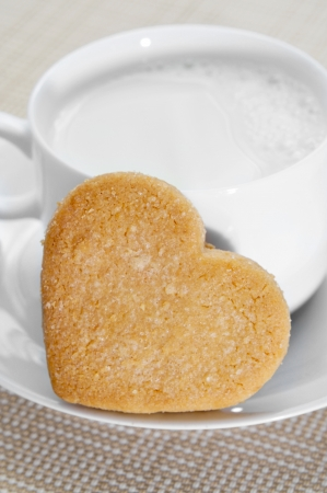 a heart-shaped shortbread biscuit and a cup of milk Stock Photo - 15402215