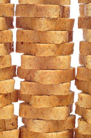some piles of whole-wheat mini toasts on a white background photo