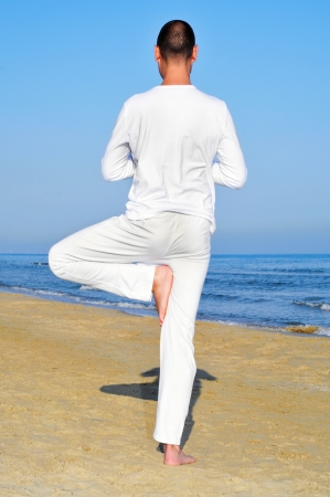 a yogi practicing the tree pose on the beach photo