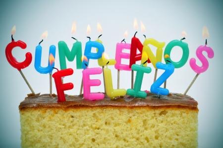 sentencia: en forma de carta-velas de diferentes colores que forman frase feliz cumplea�os, feliz cumplea�os en espa�ol, en una torta Foto de archivo