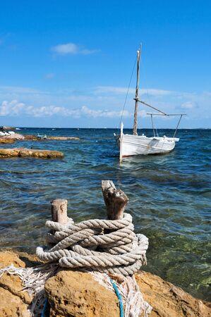 mooring: view of a fishing boat in Punta de Sa Pedrera coast in Formentera, Balearic Islands, Spain