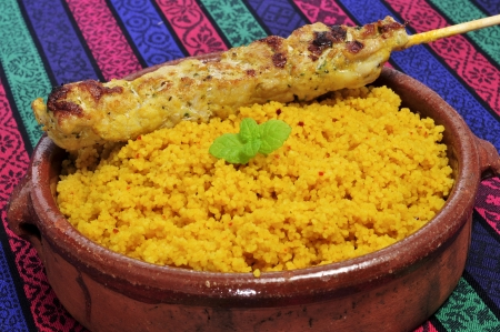 closeup of a plate with spiced couscous and a chicken skewer Banco de Imagens