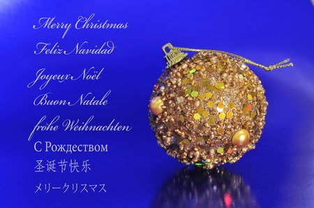 feliz: a golden christmas ball on a blue background and the sentence merry christmas written in english, spanish, french, italian, german, russian, chinese and japanese Stock Photo