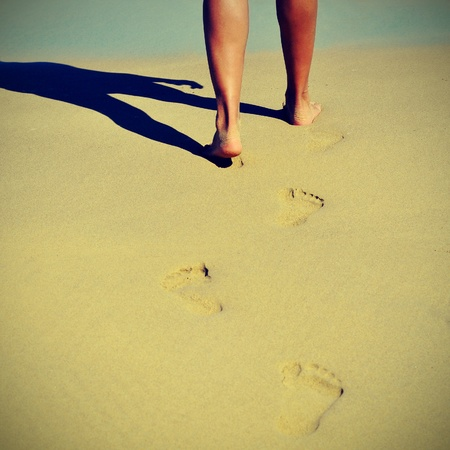 someone walking on the sand of a beach in the summer with a retro effect photo