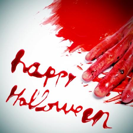 sentencia: Happy Halloween frase escrita con sangre y una mano asustadiza y sangrienta en un charco de sangre Foto de archivo