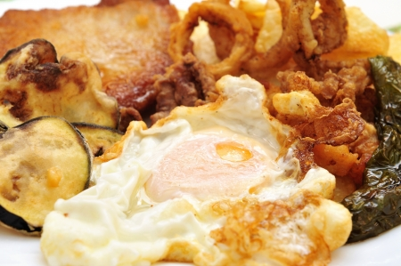 calamares: closeup of a spanish combo platter with fried egg, grilled pepper, fried calamares, breaded tenderloin and fried eggplant
