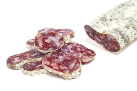 carnes: una pila de rodajas de fuet, salami español, sobre un fondo blanco