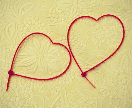 zip tie: two heart-shaped zip ties on a patterned background