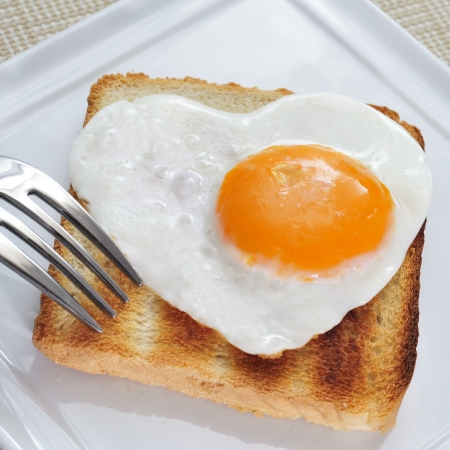 closeup of a plate with a toast with a heart-shaped fried egg photo