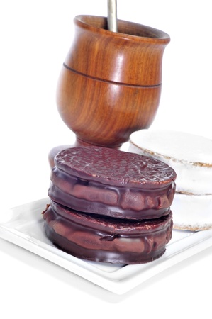 yerba mate: un plato con Argentino-Uruguaya alfajores y una infusión de mate en un recipiente de mate en un fondo blanco
