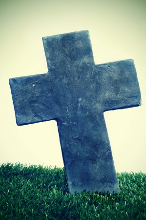 closeup of a stone cross of a grave in a cemetery for halloween photo