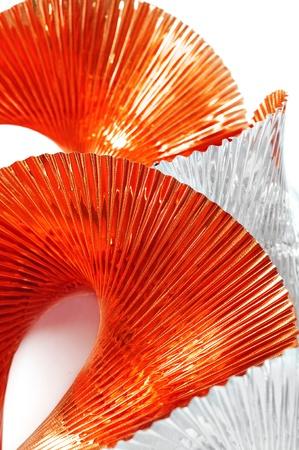 undulating: undulating red orange and silver garland on a white background