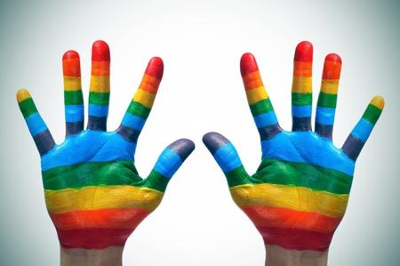 homosexuales: alguien que muestra las palmas de sus manos pintadas como la bandera del arco iris
