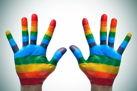 gay pride flag: someone showing the palms of his hands painted as the rainbow flag Stock Photo