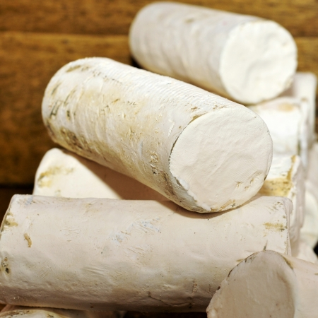 hard sell: some rolls of artisan goat cheese in a market stall Stock Photo