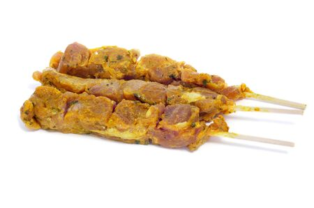 closeup of some raw pinchos de pollo, spanish chicken skewers, on a white background